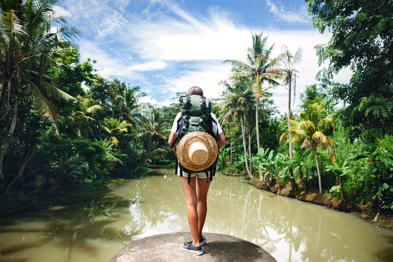 Joven con mochila en un promontorio sobre el agua en la selva.
